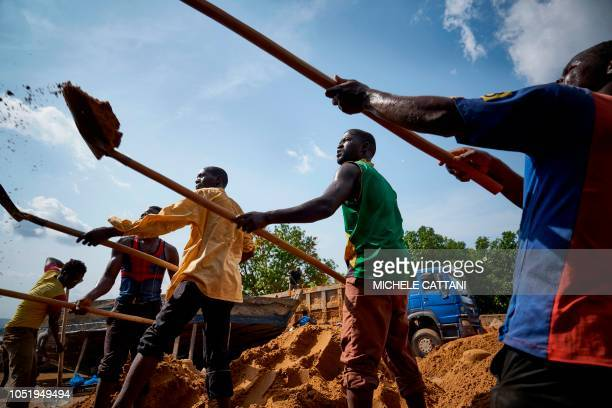 Malian workers load sand collected from the Niger river bed into a truck at the port of Bamako on October 7 2018 Increasing construction in the...