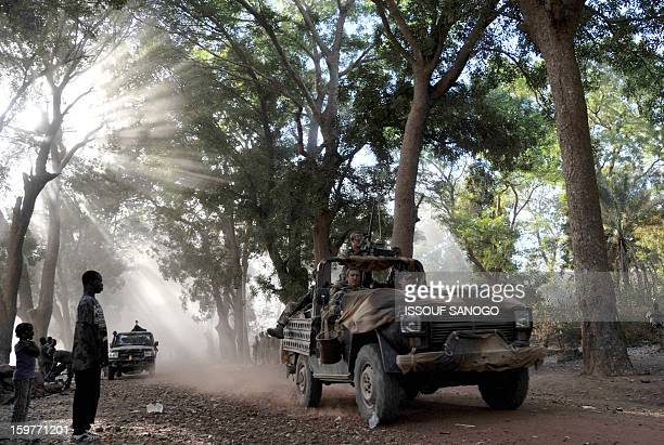 Malian youths look on as French soldiers drive down a street in Niono on January 20 2013 French Defence Minister JeanYves Le Drian said today that...
