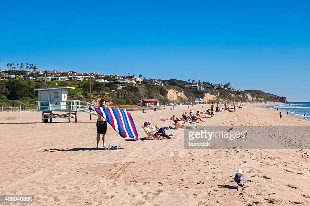 malibu, california, people suntan at zuma beach - zuma beach stock photos and pictures