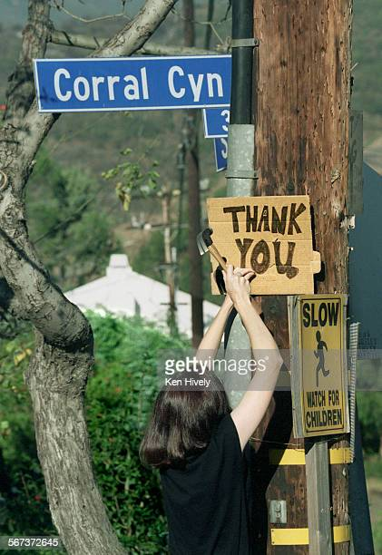Malibu resident Rann Ackerman posts a sign of appreciation to the firefighters that saved her home on Seabreeze Drive just off Corral Canyon...