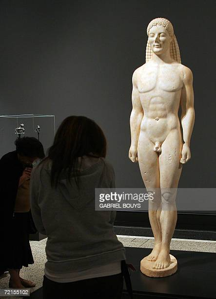 Visitors look at a Marble statue of a Kouros representing the Greek physical ideal during the Archaic period at the Getty Villa Museum in Malibu...
