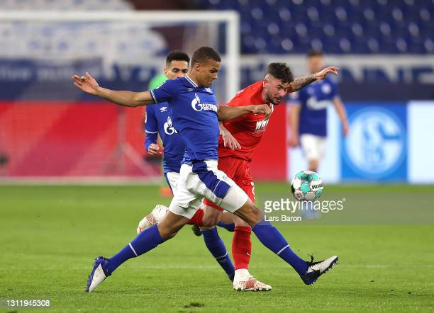 Malick Thiaw of FC Schalke 04 battles for possession with Marco Richter of FC Augsburg during the Bundesliga match between FC Schalke 04 and FC...