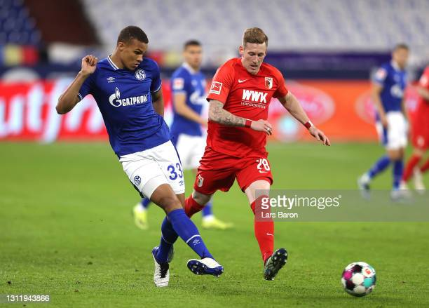 Malick Thiaw of FC Schalke 04 makes a pass whilst under pressure from Andre Hahn of FC Augsburg during the Bundesliga match between FC Schalke 04 and...