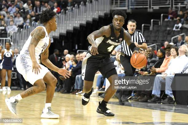 Maliek White of the Providence Friars dribbles by James Akinjo of the Georgetown Hoyasduring a college basketball game at the Capital One Arena on...