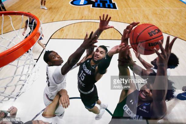 Malik Benlevi and D'Marcus Simonds of the Georgia State Panthers fight for a rebound with Tre Scott of the Cincinnati Bearcats during the game in the...