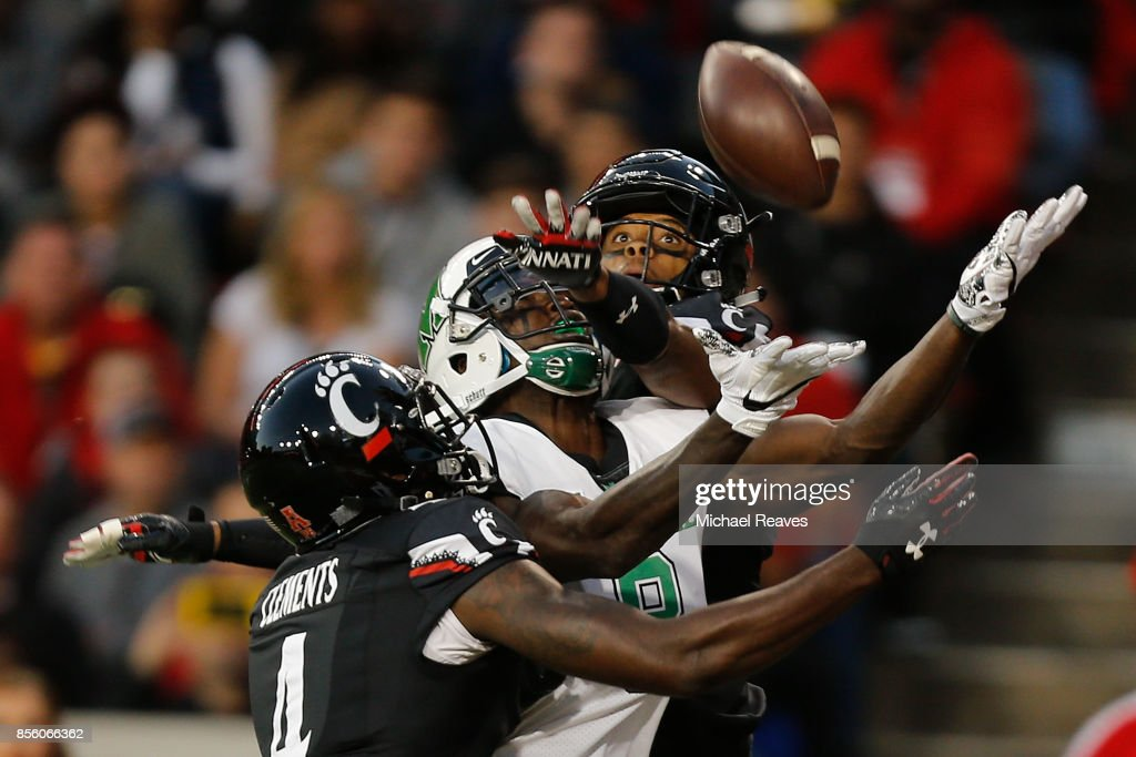 Malik Clements #4 and Linden Stephens #9 of the Cincinnati Bearcats break up a pass intended for Tyre Brady #8 of the Marshall Thundering Herd during the first half at Nippert Stadium on September 30, 2017 in Cincinnati, Ohio.