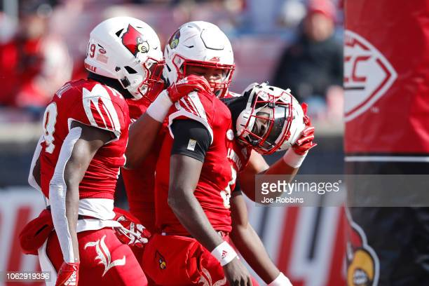 Malik Cunningham of the Louisville Cardinals celebrates with teammates in the second quarter of the game against the North Carolina State Wolfpack at...