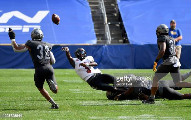 Malik Cunningham of the Louisville Cardinals throws an interception as he is hit by Calijah Kancey of the Pittsburgh Panthers in the fourth quarter...