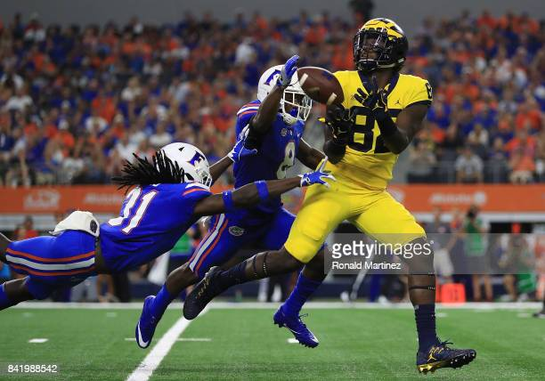 Malik Davis of the Florida Gators and Nick Washington of the Florida Gators try to break up a pass to Nick Eubanks of the Michigan Wolverines at ATT...