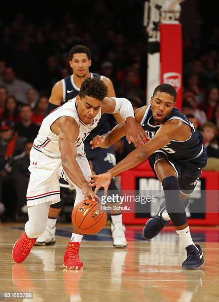 Malik Ellison of the St John's Red Storm battles Mikal Bridges of the Villanova Wildcats for a loose ball during the second half of an NCAA college...