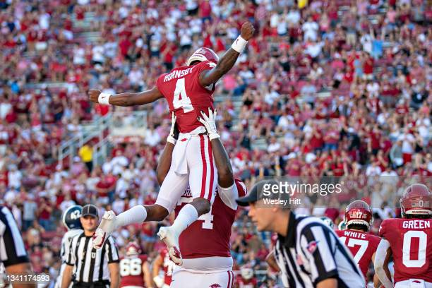 Malik Hornsby is lifted in the are by Jalen St. John of the Arkansas Razorbacks after scoring a touchdown in the second half of a game against the...