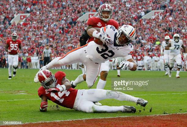 Malik Miller of the Auburn Tigers dives for a touchdown over Deionte Thompson of the Alabama Crimson Tide at BryantDenny Stadium on November 24 2018...