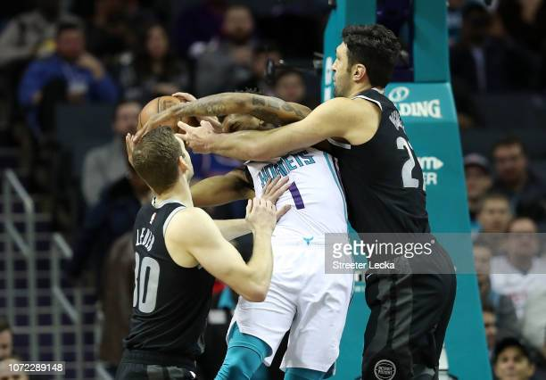 Malik Monk of the Charlotte Hornets collides with teammates Jon Leuer and Zaza Pachulia of the Detroit Pistons during their game at Spectrum Center...
