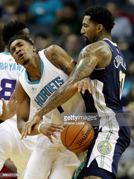 Malik Monk of the Charlotte Hornets runs into Wilson Chandler of the Denver Nuggets during their game at Spectrum Center on October 25 2017 in...