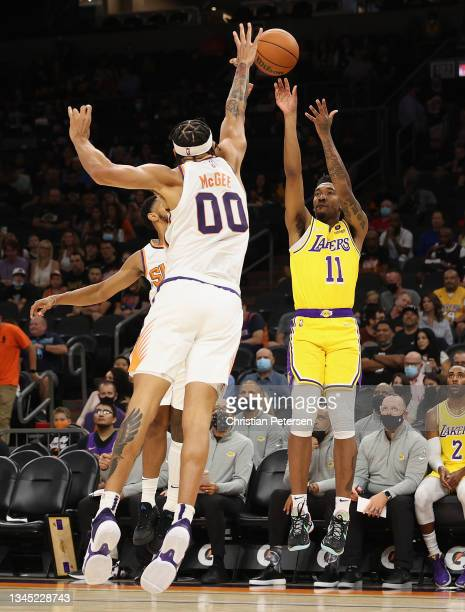 Malik Monk of the Los Angeles Lakers attempts a three-point shot over JaVale McGee of the Phoenix Suns during the first half of the NBA preseason...