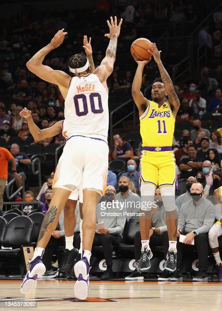 Malik Monk of the Los Angeles Lakers shoots the ball over JaVale McGee of the Phoenix Suns during the NBA preseason game at Footprint Center on...