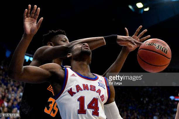 Malik Newman of the Kansas Jayhawks is fouled by Yankuba Sima of the Oklahoma State Cowboys as he takes a shot in the first half at Allen Fieldhouse...