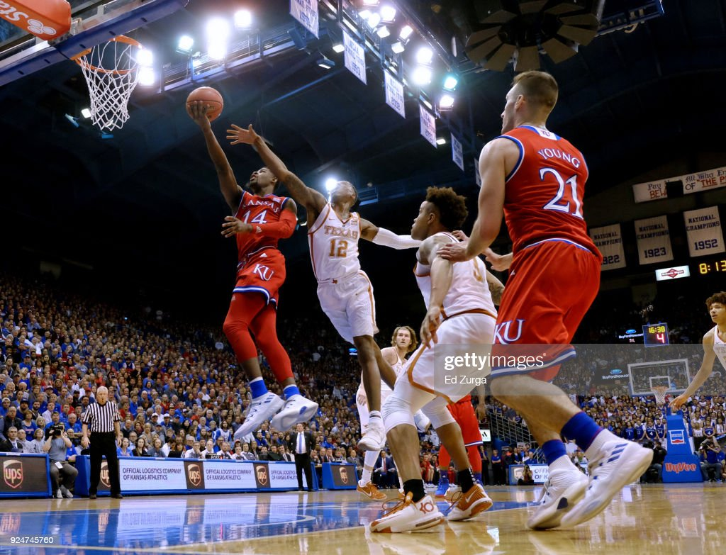 Malik Newman #14 of the Kansas Jayhawks lays the ball up against Kerwin Roach II #12 of the Texas Longhorns in the first half at Allen Fieldhouse on February 26, 2018 in Lawrence, Kansas.