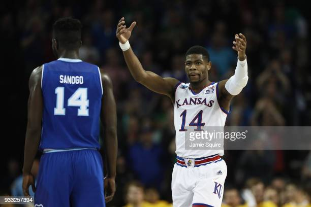 Malik Newman of the Kansas Jayhawks reacts as Ismael Sanogo of the Seton Hall Pirates looks on in the second half during the second round of the 2018...