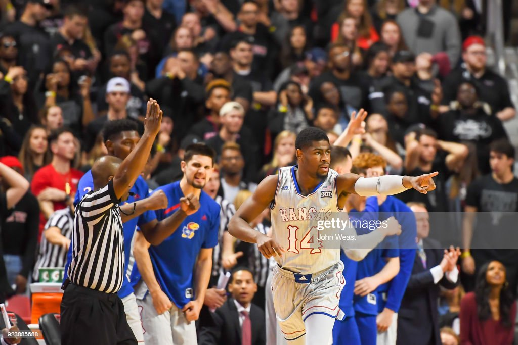 Malik Newman #14 of the Kansas Jayhawks reacts with teammates after making a three point shot during the second half of the game against the Texas Tech Red Raiders on February 24, 2018 at United Supermarket Arena in Lubbock, Texas. Kansas defeated Texas Tech 74-72.