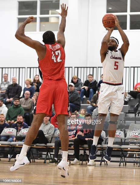 Malik Petteway of the Robert Morris Colonials puts up a shot as Alex Holcombe of the Youngstown State Penguins defends during the first half in the...