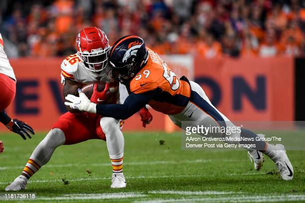 Malik Reed of the Denver Broncos tackles Damien Williams of the Kansas City Chiefs during the first quarter on Thursday, October 17, 2019.