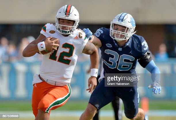 Malik Rosier of the Miami Hurricanes breaks away from Cole Holcomb of the North Carolina Tar Heels during their game at Kenan Stadium on October 28...