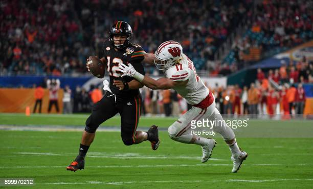 Malik Rosier of the Miami Hurricanes is stopped by Andrew Van Ginkel of the Wisconsin Badgers during the fourth quarter of the 2017 Capital One...