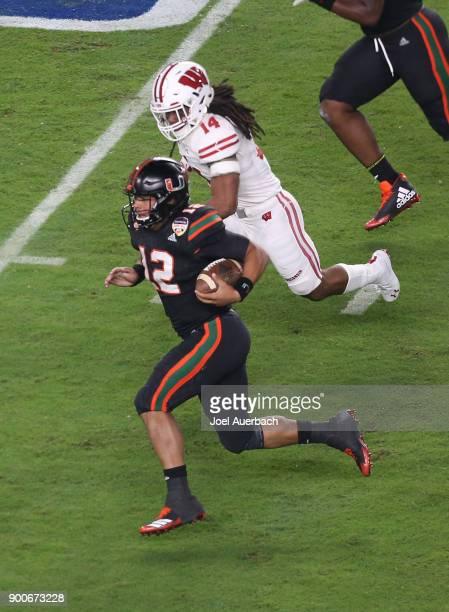 Malik Rosier of the Miami Hurricanes runs with the ball past D'Cota Dixon of the Wisconsin Badgers during the 2017 Capital One Orange Bowl at Hard...