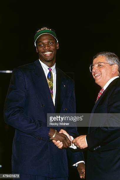Malik Sealy shakes hands with NBA Commissioner David Stern after he was selected number fourteen overall by the Indiana Pacers during the 1992 NBA...