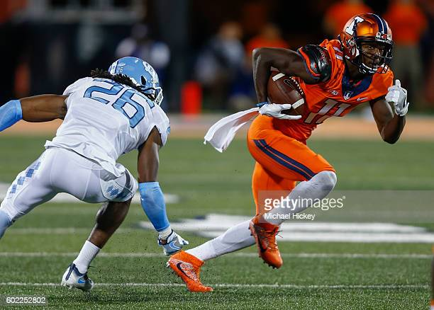 Malik Turner of the Illinois Fighting Illini runs the ball after a reception as Dominquie Green of the North Carolina Tar Heels defends at Memorial...