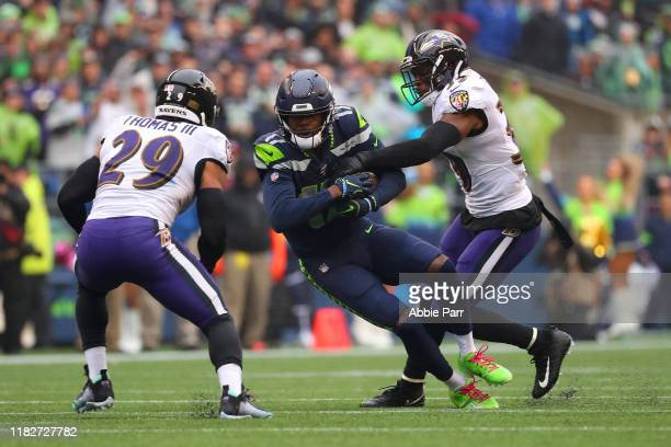 Malik Turner of the Seattle Seahawks is tackled by Brandon Carr and Earl Thomas of the Baltimore Ravens in the second quarter during their game at...