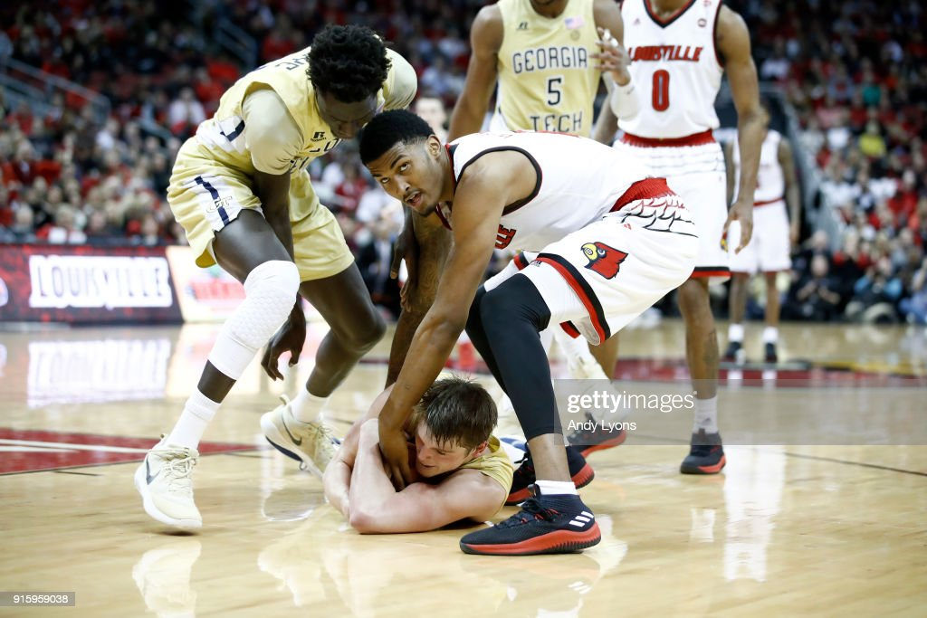 Malik Williams #5 of the Louisville Cardinals battles for a loose ball with Abdoulaye Gueye #34 (left) and Ben Lammers #44 (on floor) of the Georgia Tech Yellow Jackets during the game at KFC YUM! Center on February 8, 2018 in Louisville, Kentucky.