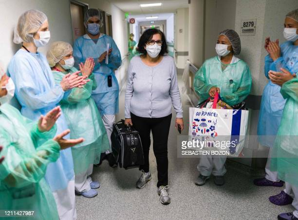 Malika Fisli , a patient suffering from the COVID-19 caused by the novel coronavirus, leaves the physical medicine and rehabilitation unit applauded...