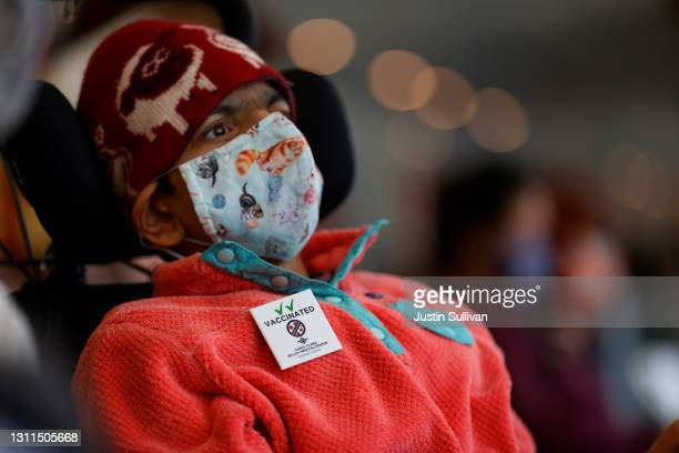 """Malika Kikkeri wears a pin that says """"vaccinated"""" after receiving the COVID-19 vaccine during a vaccination clinic for Special Olympics athletes,..."""