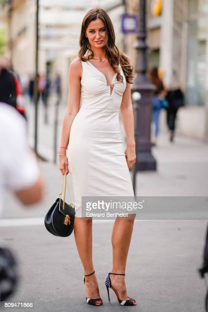 Malika Menard wears a white dress a black Chloe bag and heels outside the Jean Paul Gaultier show during Paris Fashion Week Haute Couture Fall/Winter...