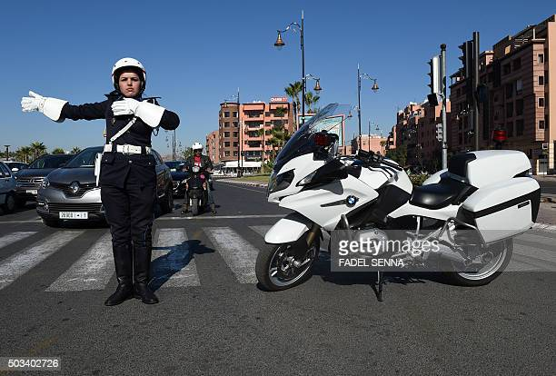 Malika Oumoulid a Moroccan member of the female police motorbike brigade controls the traffic in the Western city of Marrakesh on December 19 2015...