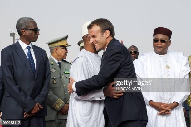 Mali's President Ibrahim Boubacar Keita embraces French President Emmanual Macron as Niger president Mahamadou Issoufou looks on before a working...