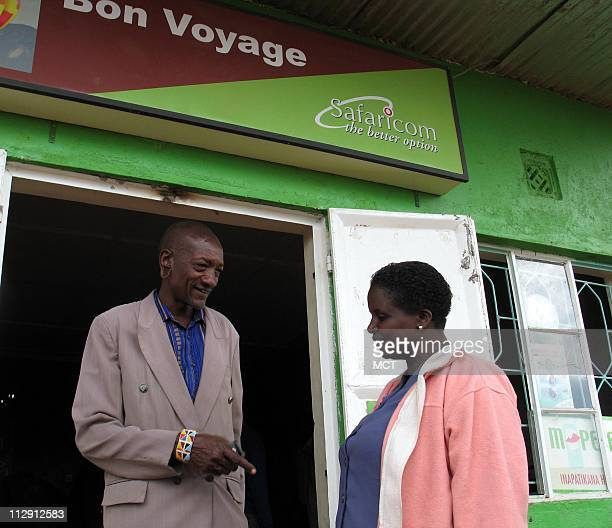 Malit Kuronoi left and his sisterinlaw Charity stand outside an MPesa office in Ntulele Kenya after sending money via the innovative cell phone...