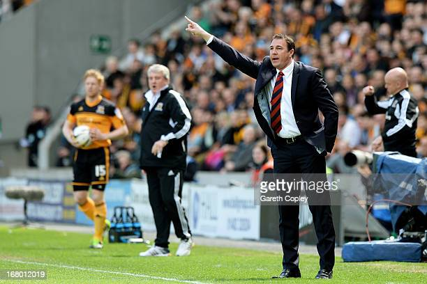 Malky MacKay the Cardiff manager shouts instructions to his players as Steve Bruce the Hull manager looks on during the npower Championship match...