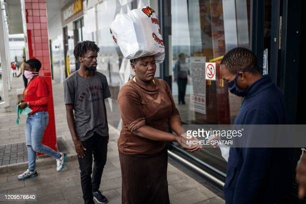 A mall clerk sanitises a customer's hands at the entrance of a shopping mall in Alexandra Johannesburg on April 10 2020 Alexandra township local...