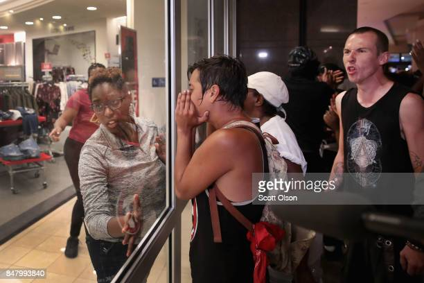 A mall employee shuts the doors to Macy's department store as demonstrators march through the West County Mall protesting the acquittal of former St...