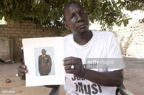 Malleh Jagne a victim of Gambia's former regime poses with a picture of his late younger brother Lamin at his home in Serekunda on April 5 2017...