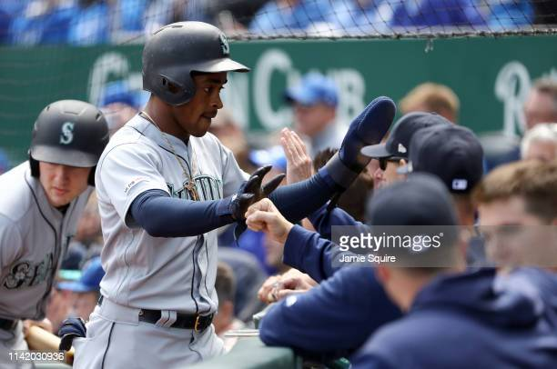 Mallex Smith of the Seattle Mariners is congratulated by teammates in the dugout after scoring during the game against the Kansas City Royals at...