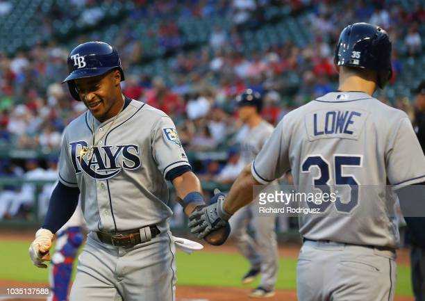 Mallex Smith slaps hands with Brandon Lowe of the Tampa Bay Rays after scoring on a single by JiMan Choi in the first inning against the Texas...