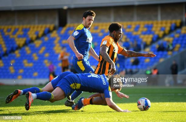 Mallik Wilks of Hull City is tackled by Alex Woodyard of AFC Wimbledon leading to a penalty during the Sky Bet League One match between AFC Wimbledon...