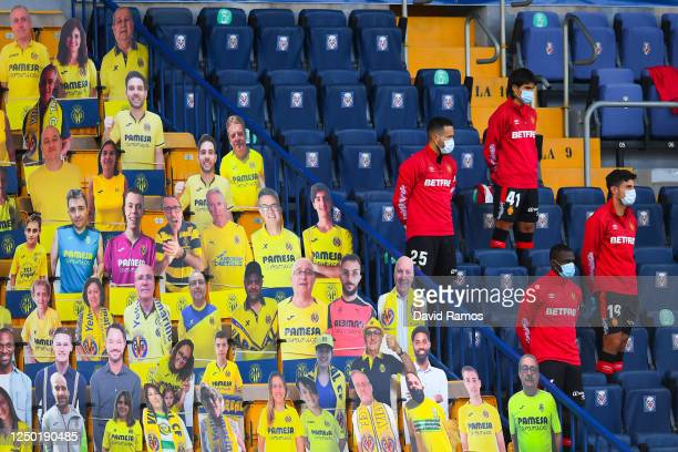 Mallorca substitutes observe a minute of silence in memory of the victims of COVID-19 next to cardboard cut outs of Villarreal supporters in the...