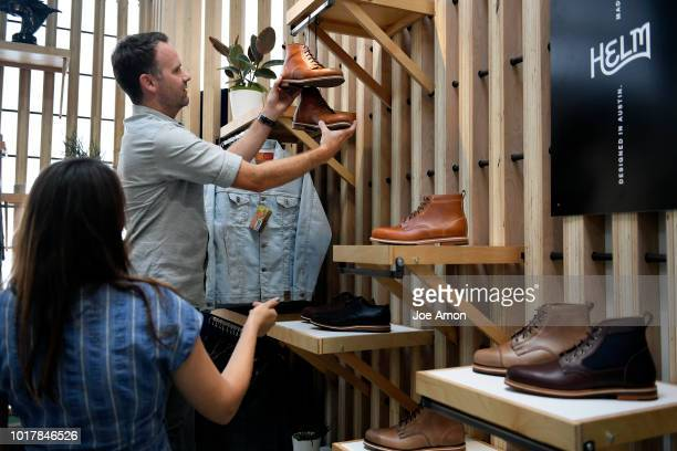 Mallory Hublein studio manager, helping Brad Day, president of Helm Boots, arrange their display at Eyes Open in the expanded Source Market Hall on...