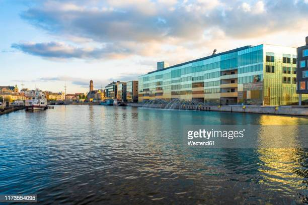 malmo university by harbor against sky in city - malmo stock pictures, royalty-free photos & images