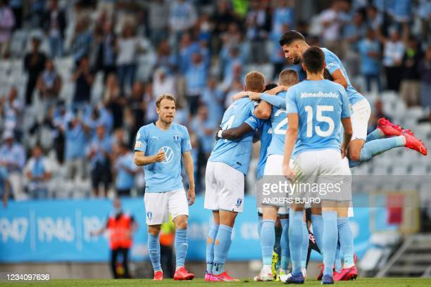 Malmo's Danish midfielder Anders Christiansen is celebrated by teammates for scoring 2-1 during the UEFA Champions League qualifying football match...